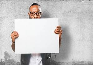 Guy holding a blank poster with wall background Photo ...
