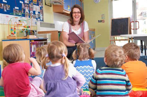 group  pre school children listening  teacher reading