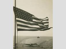 The American flag flies above the rear deck of an aircraft