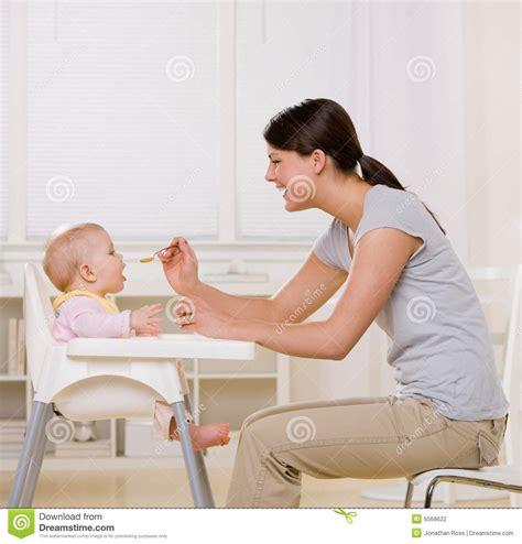 feeding baby in highchair in kitchen stock photo