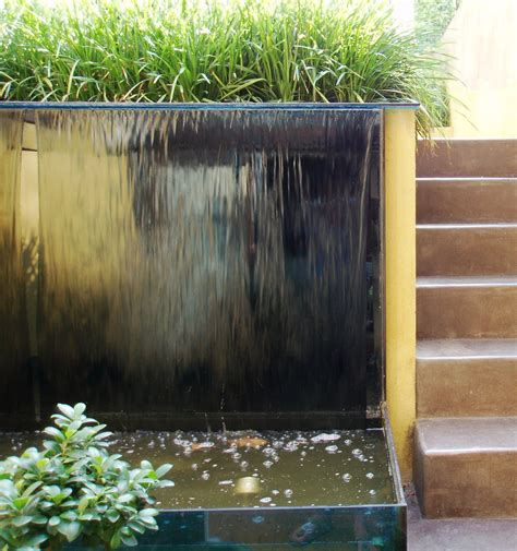 glass water feature garden with glass water wall and polished concrete steps simon scott landscaping