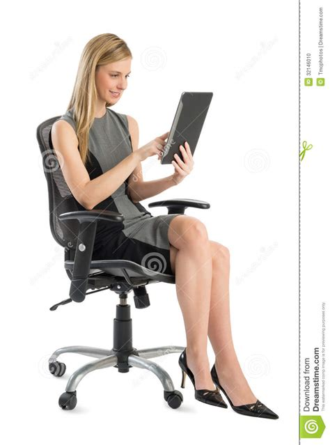 businesswoman using digital tablet while sitting on office