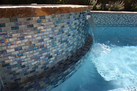 iridescent blue 1 x 2 glass tile surrounds the pool and