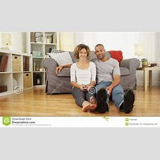 Cute African Couple Sitting On Floor In Living Room Stock