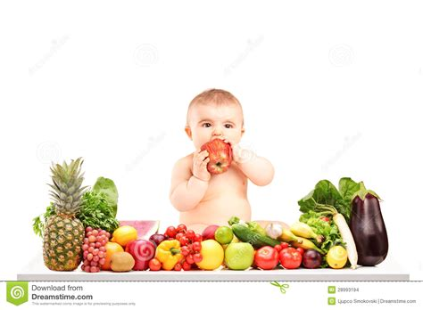 Cute Baby Boy Sitting On A Table With Fruits And