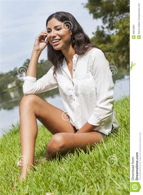 Latina Woman Girl Sitting On Grass By Lake In Summer Stock