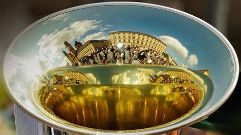 A marching band is reflected in the bell of a horn during ...