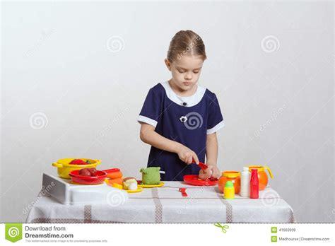jouet cuisine fille la fille coupe un chignon de jouet dans la cuisine