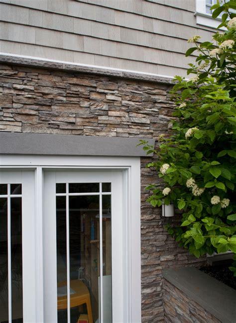 stacked stone exterior  white window trimming