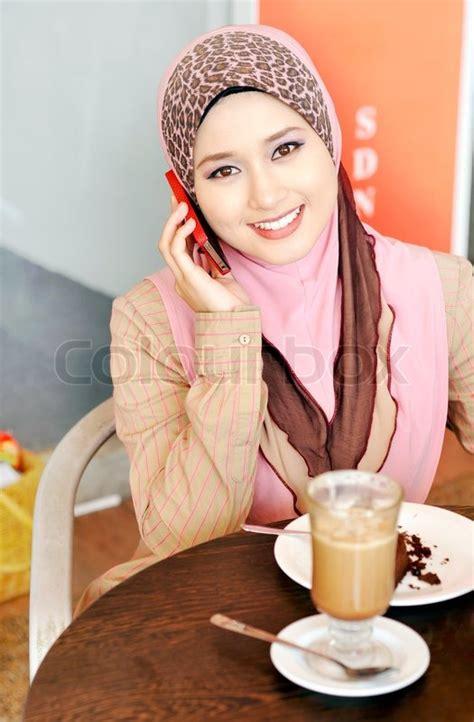 pretty muslim girl calling  friend stock photo