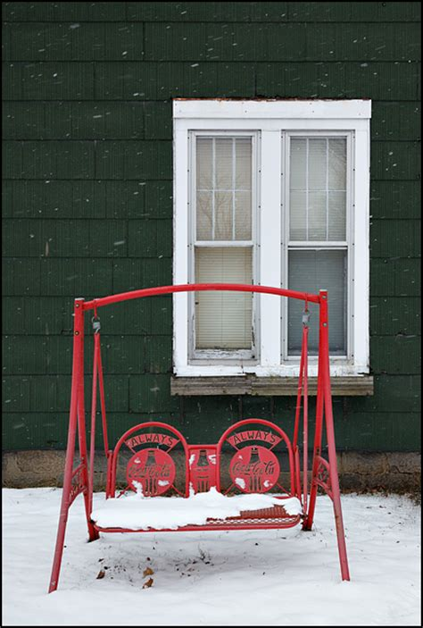 coca cola porch swing in front of an house in a