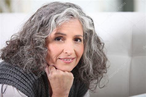 grijs haired vrouw kin op hand rusten stockfoto