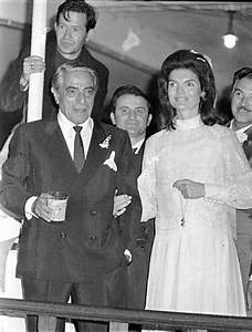 Jacqueline Kennedy Onassis holds the arm of her new ...