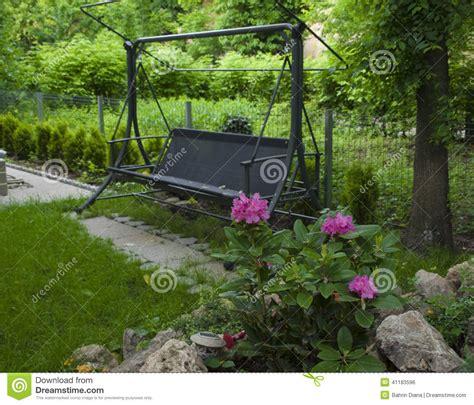 Swing Bench In Lush Garden Stock Image