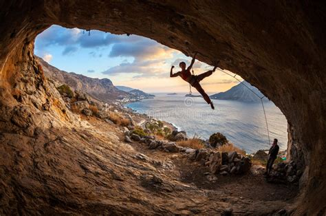 Female Rock Climber Posing While Climbing Stock Photo