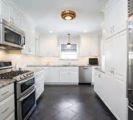 white kitchen cabinets with black and gray granite