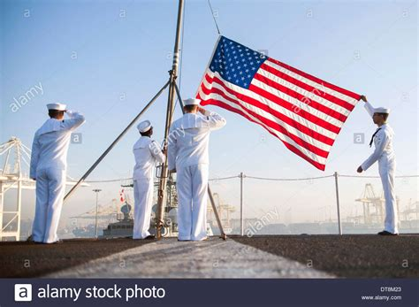 morning colors us navy sailors raise the american flag during morning