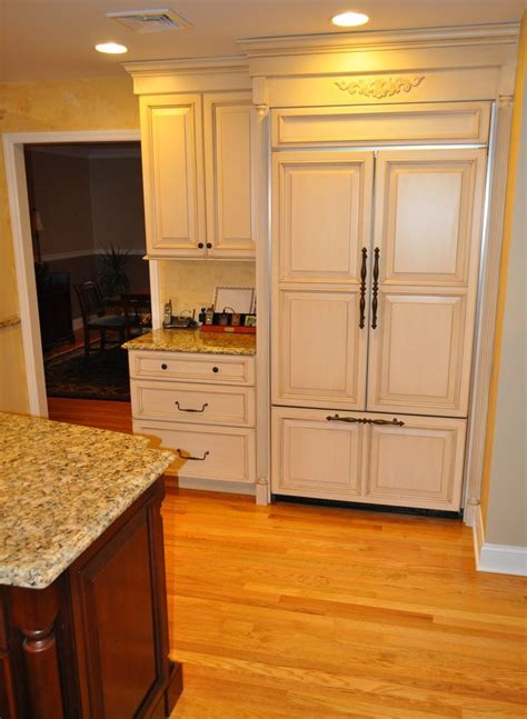 wood paneled refrigerator with a wall cabinet and base