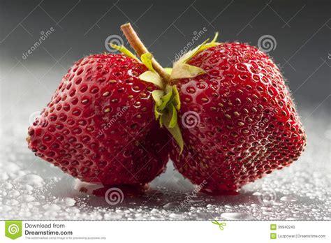 twin strawberries studio shot wet background minimalist