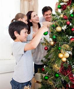 Young Family Decorating A Christmas Tree Royalty Free ...