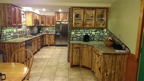 rustic cedar kitchen cabinets rustic red cedar kitchen with cultured stone backsplash
