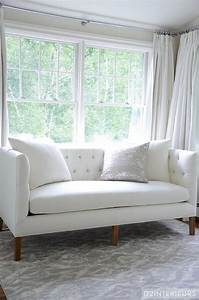 white and grey bedroom with white tufted sofa With sofa in front of bed