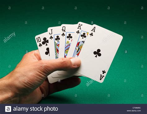 A Man's Hand Holding Playing Cards On A Green Table. A
