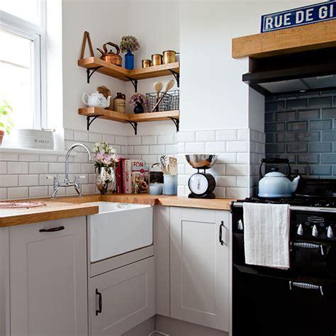 White kitchen corner with metro tiles and wooden worktop