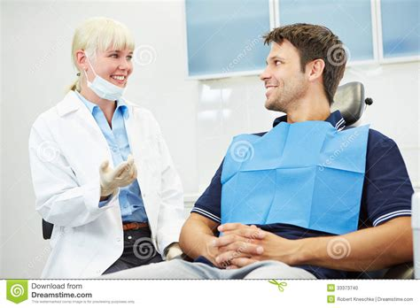 dentist talking with patient on chair stock photo image