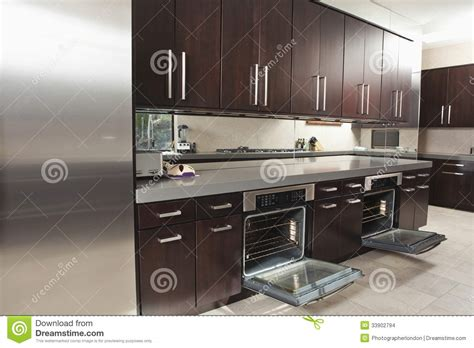 commercial kitchen with open oven and cabinets stock