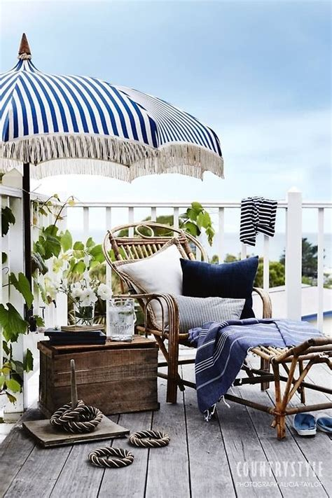 a navy and white striped umbrella rattan chaise