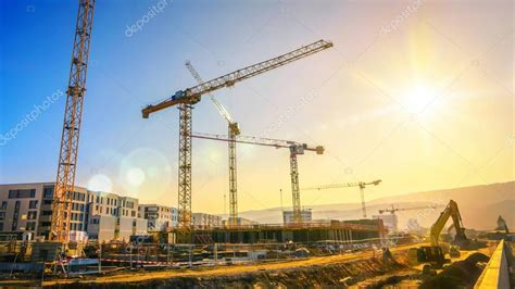 Large construction site including several cranes, with ...