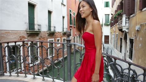 happy beautiful woman in red summer dress walking over canal bridge smiling in venice italy
