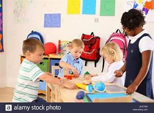 Four kids playing in preschool classroom Stock Photo ...