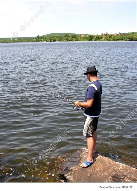 young man fishing   rocks picture