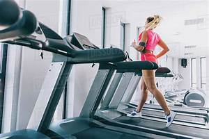 Side View Of Woman Running On Treadmill At Gym In 2020