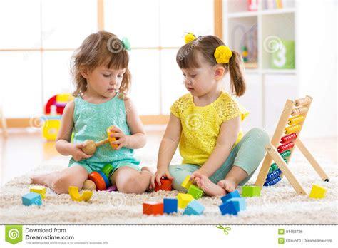 children in a kindergarten vector illustration 294 | children playing together building blocks educational toys preschool kindergarten kids little girls build pyramid 91483736
