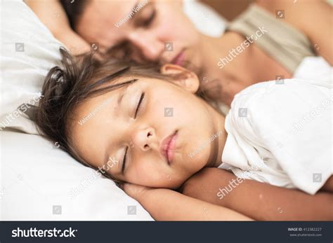Sleeping Kid Girl And Her Mother In The Bed Stock Photo