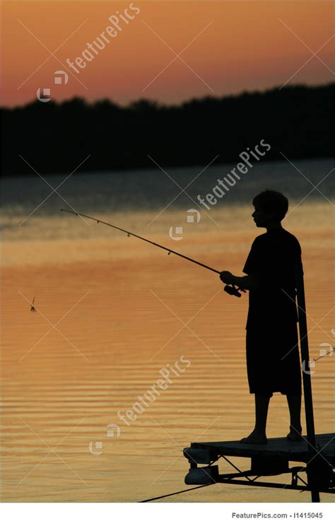 silhouette  young boy fishing  pier stock image
