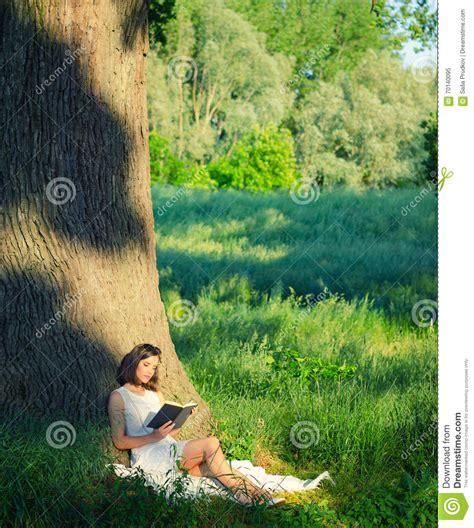 beautiful young girl sitting  giant oak  reading