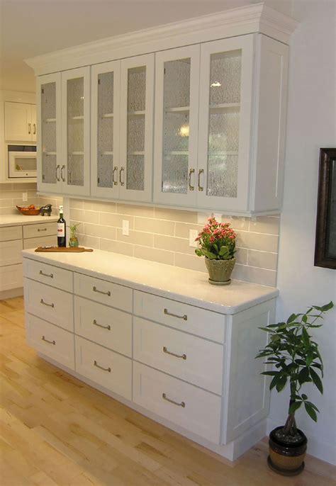 woman standing  tall aisle kitchen  white brick wall white shaker cabinets