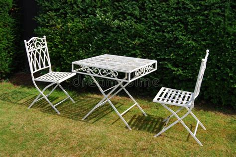 White Metal Garden Furniture Table And Two Chairs Stock