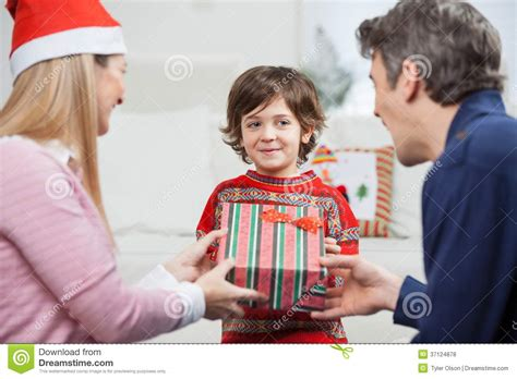 what to give to parents for christmas boy receiving gift from parents stock photo image of evening 37124878