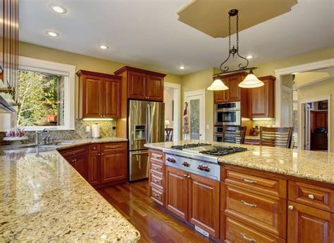 When staining oak cabinets, consider colors such as golden oak, maple, colonial oak, and pecan. This traditional kitchen contains warm, oak cabinets and ...