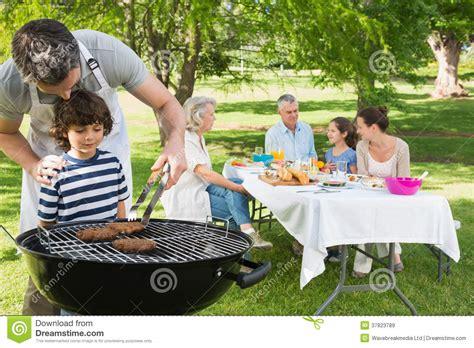 la cuisine au barbecue le père et le fils au barbecue grillent avec la famille