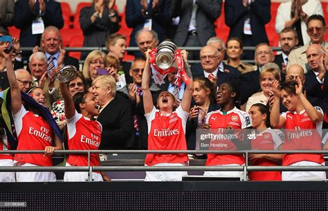 Kelly Smith of Arsenal lifts the trophy with team mates ...