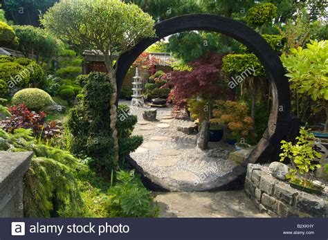 japanese style garden with moon gate rocks shrubs and