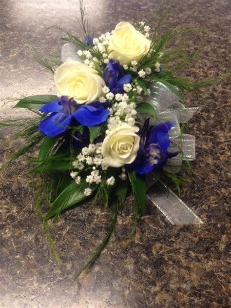 White sweetheart rose corsage with baby's breath blue