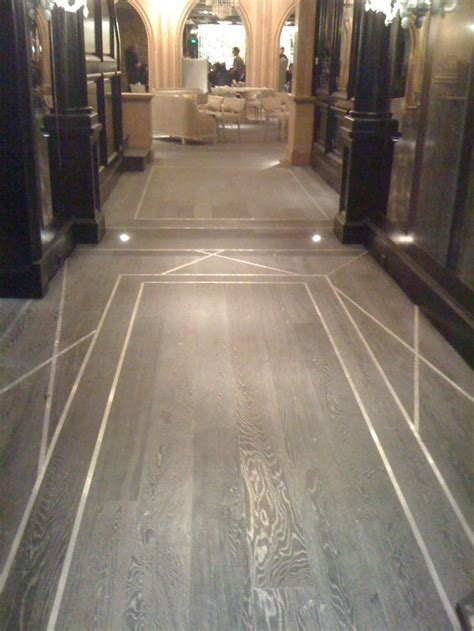 Use metal inlay to delineate foyer area in subtle way