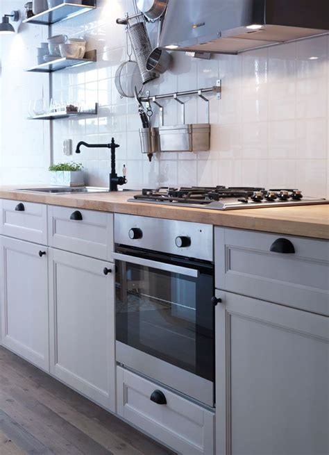 Traditional white IKEA kitchen with wood worktops, black